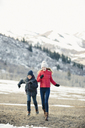 A brother and sister running across the grass together n winter. - MINF02891
