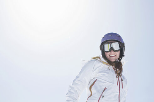Young woman wearing ski goggles and helmet - ISF17678