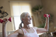 Older woman lifting weights at home - ISF17720