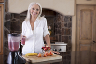 Older woman making smoothie in kitchen - ISF17723