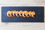 Row of shrimps on slate, salt - GIOF03996