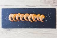 Row of shrimps on slate, salt - GIOF03996