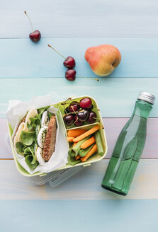 Healthy school food in a lunch box, vegetarian sandwich with cheese, lettuce, cucumber, egg and cress, sliced carrot and celery, cherries and pear - IPF00464