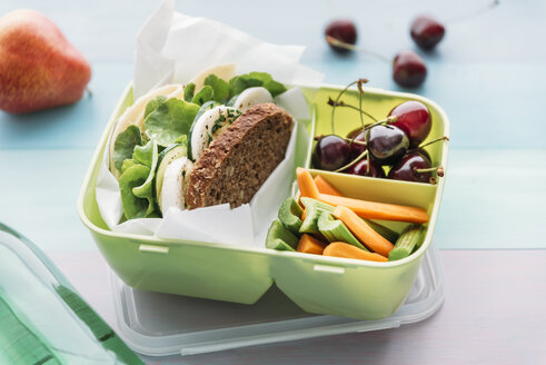 Healthy school food in a lunch box, vegetarian sandwich with cheese, lettuce, cucumber, egg and cress, sliced carrot and celery, cherries and pear - IPF00467