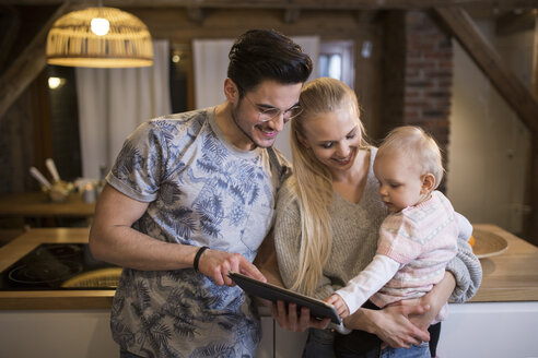 Happy young parents using tablet at home with their baby girl - AWF00129