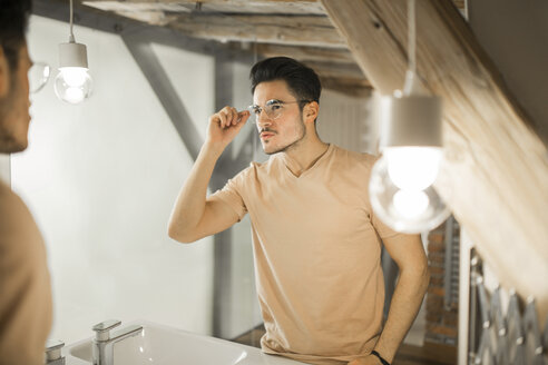 Young man looking in bathroom mirror - AWF00141