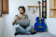 Man in his room with mobile phone, laptop and bass guitar - KIJF01973