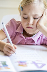 Portrait of bored little girl writing numbers in exercise book - JFEF00895