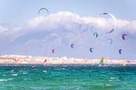 Spain, Andalucia, Tarifa, windsurfers and kite surfers on the sea with mountains of Morocco in the background - SMAF01086