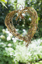 A heart shape made out of woven twigs, hanging from a tree. Simple decorations. - MINF02966