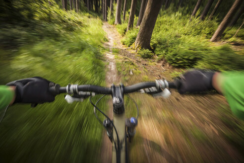 Mountain biker speeding down forest path - ISF18043