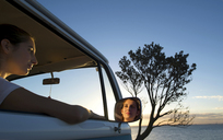 Young woman looking out of camper van window at dusk - ISF18130