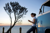 Young woman leaning on camper van at dusk - ISF18133