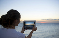 Young woman photographing with her digital tablet at sunset - ISF18136