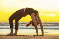 Woman practicing yoga on beach - ISF18220