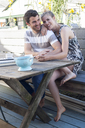 Couple at patio table, Breezy Point, Queens, New York, USA - ISF18328