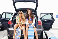 Female friends sitting in car boot with skateboards - ISF18346