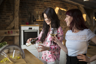 Happy female friends at home drinking white wine - AWF00146