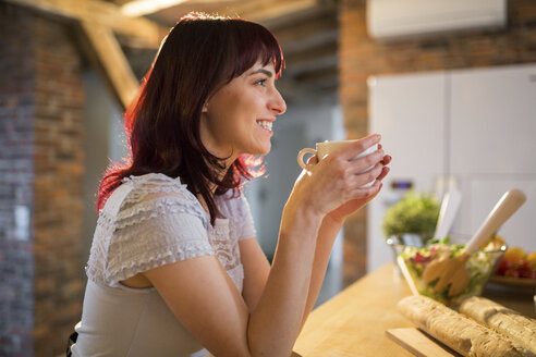 Smiling woman drinking cup of coffee in kitchen at home - AWF00158