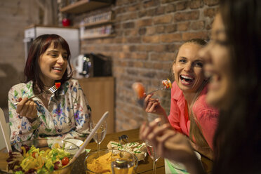 Happy female friends having dinner at home together - AWF00164