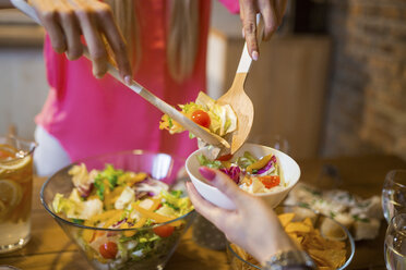 Close-up of woman dishing up salad for friend during dinner at home - AWF00170
