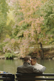 Gay couple hugging on park bench - ISF18489