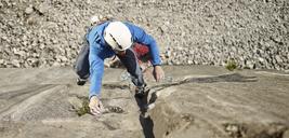 Austria, Innsbruck, Martinswand, man climbing in rock wall - CVF00995
