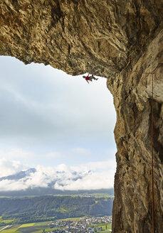 Austria, Innsbruck, Martinswand, man climbing in grotto - CVF01004