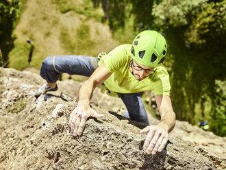Austria, Innsbruck, Hoettingen quarry, man climbing in rock wall - CVF01016