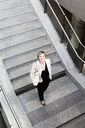 Smiling businesswoman walking downstairs - GIOF04004