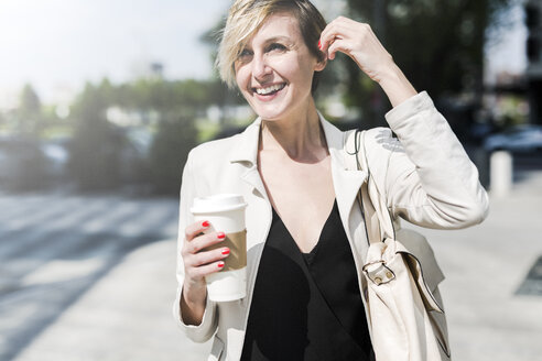 Portrait of laughing businesswoman with Coffee to go - GIOF04022