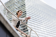 Businesswoman leaning on railing looking at distance - GIOF04028