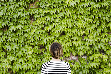 Back view of woman in front of facade greenery - GIOF04037