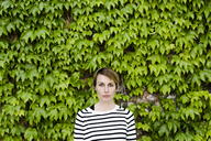 Portrait of woman in front of facade greenery - GIOF04040