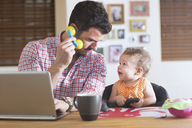 Man and baby sitting at kitchen counter playing with smartphone and toy phone - ISF18544