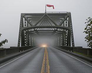 Car emerging from misty bridge - ISF18553