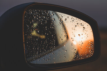 Raindrops reflecting on rear-view mirror of car during sunset - ACPF00146