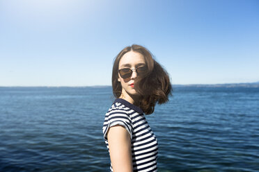 Italy, Lake Garda, portrait of young woman with brown hair wearing sunglasses - GIOF04045