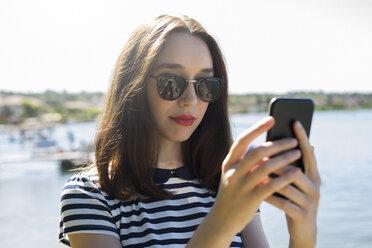 Italy, Lake Garda, portrait of young woman wearing sunglasses using smartphone - GIOF04048