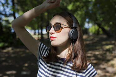 Portrait of young woman wearing sunglasses listening music with headphones - GIOF04051