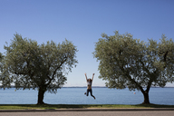Italy, Lake Garda, happy young woman jumping in the air between two trees - GIOF04054