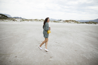 South Africa, Western Cape, Noordhoek, happy woman on the beach - DAWF00676