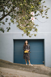 Woman wearing multicolored dress standing at garage door - DAWF00694