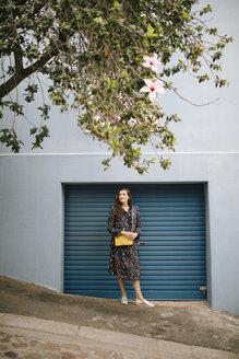 Woman wearing multicolored dress standing at garage door - DAWF00694