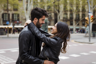 Spain, Barcelona, happy young couple hugging on the street - MAUF01541
