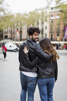 Spain, Barcelona, young couple embracing and walking in the city - MAUF01547