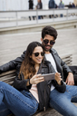 Spain, Barcelona, happy young couple with cell phone resting on a bench - MAUF01556