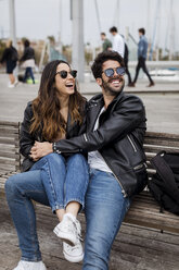 Spain, Barcelona, happy young couple resting on a bench - MAUF01559