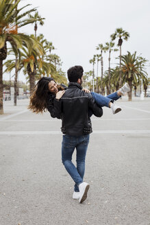 Spain, Barcelona, young man carrying happy girlfriend on promenade with palms - MAUF01562