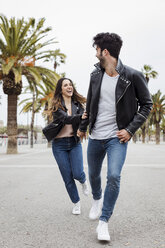 Spain, Barcelona, happy young couple running on promenade with palms - MAUF01565